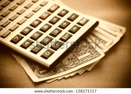 Calculator and dollars. Sepia image.