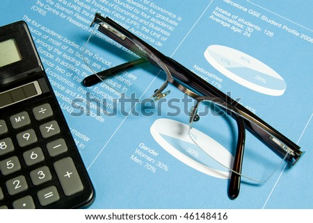 Calculator and glasses in blue finance analyzing