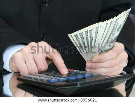 calculator and money in hand - stock photo