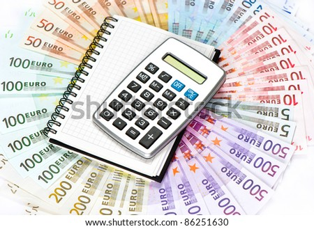 calculator and note book over euro banknotes