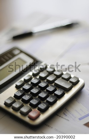 calculator and numbers with pen on the table