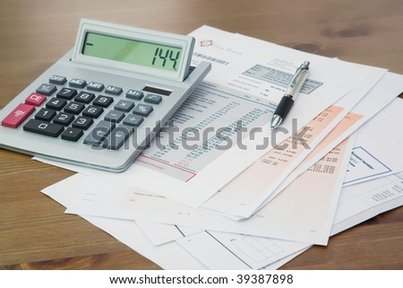 Calculator and Pen on Bank statement and credit card statements on a Wooden table