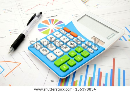 Calculator and pen on business chart