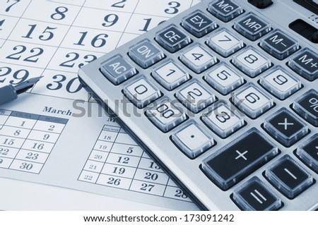 Calculator and pen on calendar background