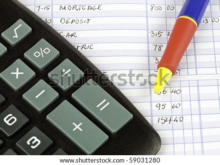 Calculator and pen used to balance checkbook - stock photo