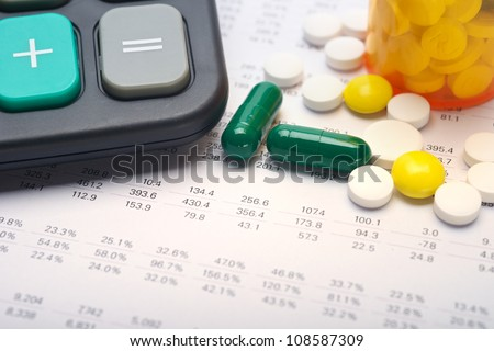 Calculator and pills on account paper background