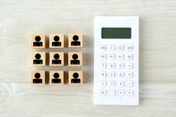 Calculator and wooden blocks with  human pictogram