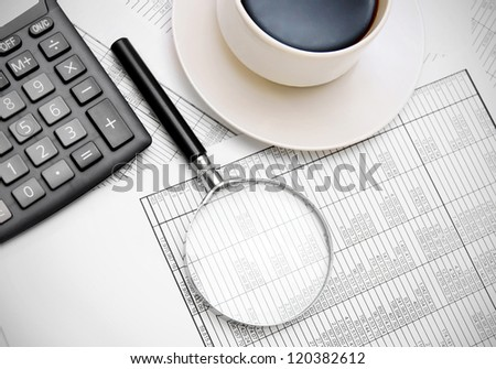 Calculator, coffee, magnifier on documents.