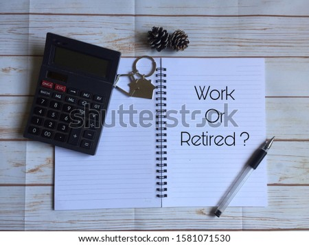 "Calculator, dried pinecones, house keychain, pen with notebook written with text ""Work or Retired"" on wooden table. Work or Retired concept."