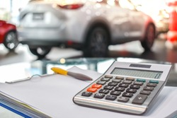 calculator for business finance on car showroom blurry background.for automotive or transportation