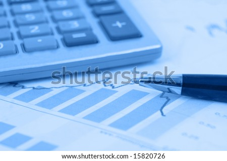 Calculator in background. Pen is focus on stock graphs