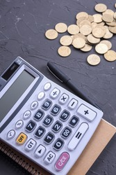 Calculator keypad on a beton floor background. Top view. Copy space.Notebook, pen, glasses And a small artificial plant