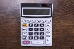 Calculator keypad on a wooden floor background. Top view. Copy space