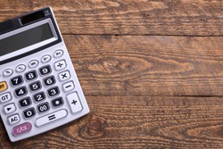Calculator keypad on a wooden floor background. Top view. Copy space.