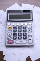 Calculator keypad with checks from the store from shopping on a wooden floor background. Top view. Copy space