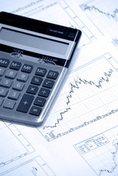 Calculator laying on printed stockcharts with bullish trend.