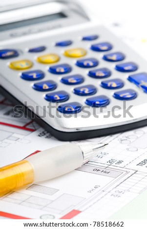 calculator lying on a plan of a house with a pen
