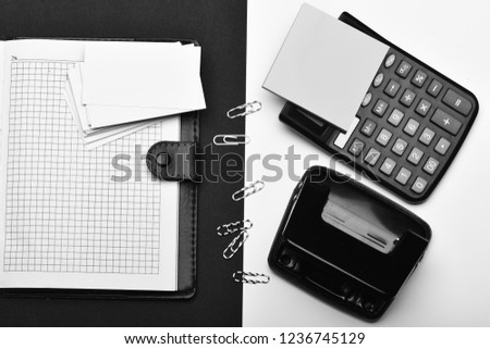 Calculator, note paper, hole punch and paper clips opposite organizer. Business and work concept. Stationery and leather covered notebook with blank pages.  Office tools on black and white background.