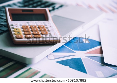 Calculator on a laptop keyboard with many charts and graphs. Reflection light and flare. Concept image of data gathering and statistical working.  #609107882