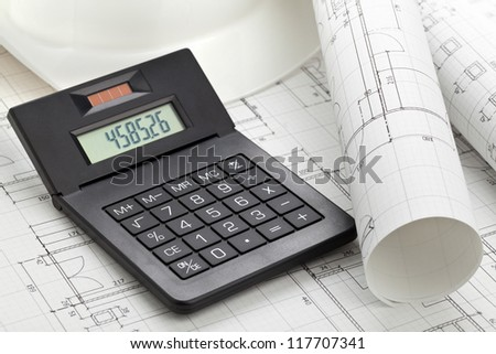 Calculator on house construction blueprints with hardhat