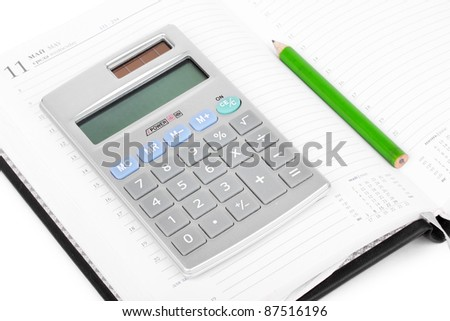 Calculator on notebook, closeup on white