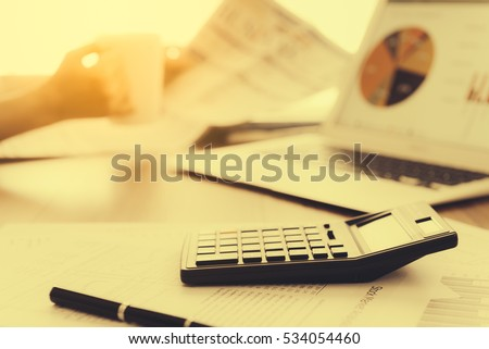 Calculator on the desk with a laptop and a background of businessman drinking coffee and reading the newspaper in the morning light. Stock photo ©