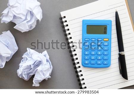 Calculator,pen,notebook,crumpled paper of Business frustrations , Job stress , top view