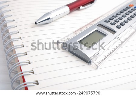 Calculator, pen, white paper for notes lie on white background