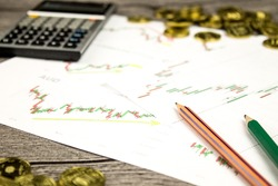 calculator,pencils and coins on graffica the Dow Jones on forex market at grey table