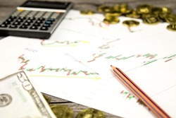 calculator,pencils,banknote and coins on graffica the Dow Jones on forex market at grey table