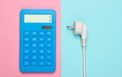 Calculator with a power plug on pink blue background. Calculation of energy consumption costs. Top view