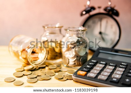 Calculator with coin in currency glass jar and clock on wooden table. Compound interest rate calculation. Financial business plan. Time investment. Saving money concept Stock photo ©
