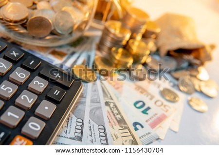 Calculator with currency glass jar and gold coins stack, dollar and euro banknotes on the table. Compound interest rate calculation or financial investment business concepts