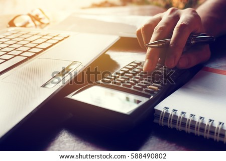 Calculator with hand's man calculate finance on desk at home office.