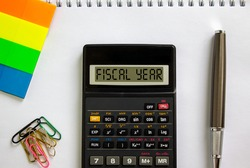 Calculator with inscription 'fiscal year', white note, colored paper, paper clips, pen. Business concept.