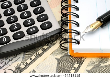 Calculator with notepad and pen on money background