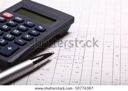 calculator with pen and calculations