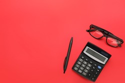 Calculator with pen and eyeglasses on color background