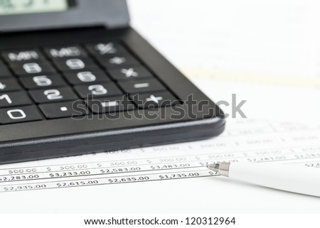Calculator with pen on paper sheets with numbers - finance expenses or budget concept