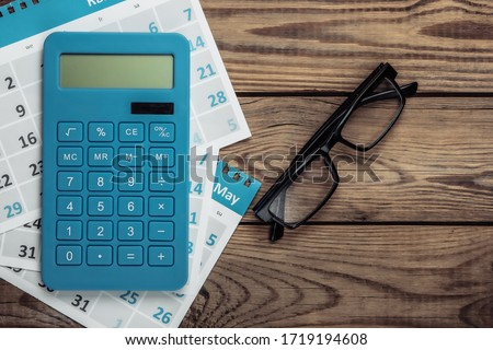 Calculator with sheets of the monthly calendar, glasses on wooden background. Economic calculation, costing. Top view