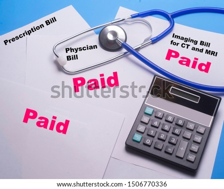 Calculator with stethoscope on a pile of paid bills .