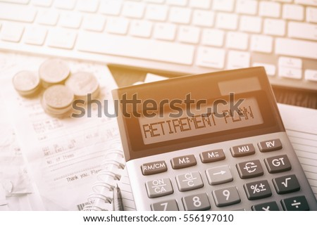 Calculator with text Retirement Plan. Calculator, currency, book, bills and computer keyboard on wooden table. Business, finance, banking conceptual.