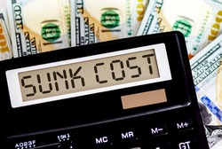 Calculator with text SUNK COST on dollars. Business, finance conceptual.