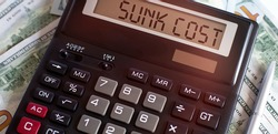 Calculator with text SUNK COST on the dollars. Business, finance conceptual.