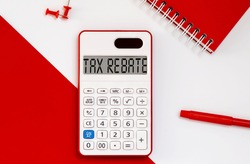 calculator with the word Tax Rebate on display with red notepad and office tools