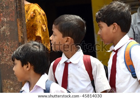 CALCUTTA, INDIA - JUNE 15: Group of young boys wait for school-bus June 15, 2008 in Calcutta, India. The boys are dressed in the traditional school uniform.