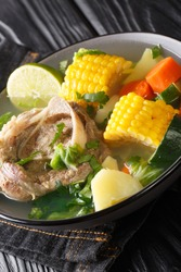 Caldo de Res is a Mexican beef soup made with a flavorful beef broth and filled with lots of vegetables such as squash, corn, carrots, cabbage and potatoes closeup in the plate on the table. Vertical