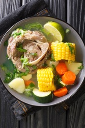 Caldo de Res is a Mexican beef soup with lots of vegetables such as squash, corn, carrots, cabbage and potatoes closeup in the plate on the table. Vertical top view from above