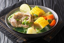 Caldo de Res is a traditional Mexican beef soup made with beef shanks and choice of vegetables closeup in the plate on the table. horizontal