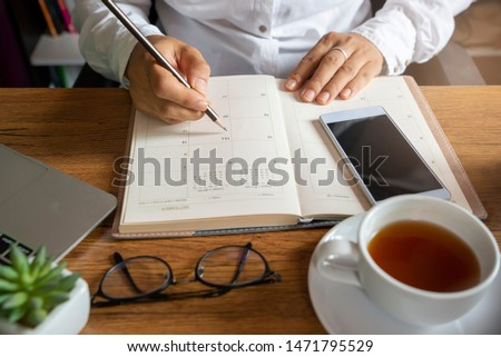 Calendar and diary, Planner writing daily appointment. Woman plan and noted schedule book (holiday trip) on book at home office. Calendar reminder event for planner concept